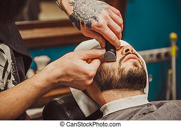 man shaving his beard in the professional hairdresser -...