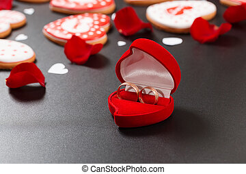Beautiful red roses petals and wedding rings on a black...
