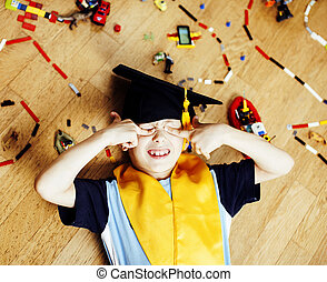 little cute preschooler boy among toys lego at home education in