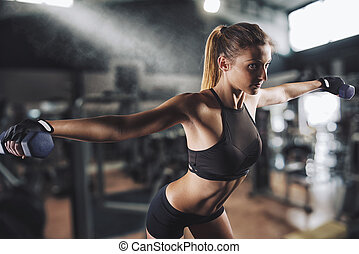 Workout at the gym - Muscular woman is training at the gym