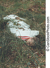 Murder victim lying on grassy field under sheet - Young male...