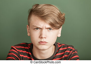 Petulant young teenage boy with a fierce scowl glaring at...