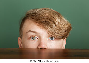 Boy with blond quiff looking over desk