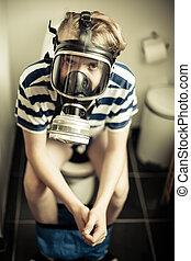 Young boy on toilet wearing gas mask - Three quarter body...