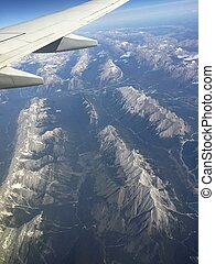 Aerial view of rocky mountains and airplane wing