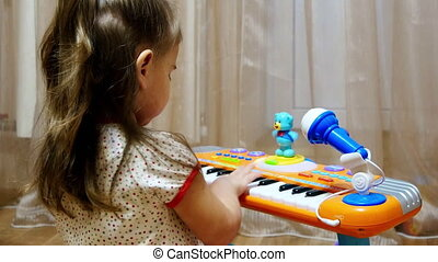 Child little girl playing on a toy piano