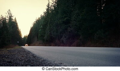 Car Passes On Rural Highway At Dusk - Car drives past...