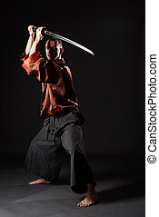 Man in chinese costume with sword studio portrait - Man...