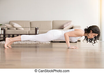 Young woman in chaturanga dandasana pose, hotel cozy living...