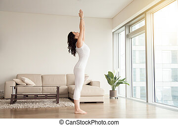 Young attractive woman in Tadasana pose, cozy hotel living...
