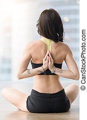 Rear view of woman in Ardha Padmasana pose with mudra -...