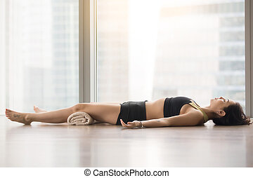 Young attractive woman in Savasana pose against floor window...