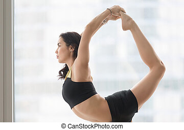 Young attractive woman in Natarajasana pose against floor window