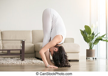 Young attractive woman in uttanasana pose, at hotel living...