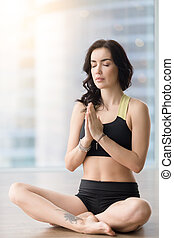 Young attractive woman in Sukhasana pose against sunny floor...