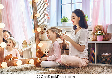 Mother is combing her daughter's hair - Happy loving family....
