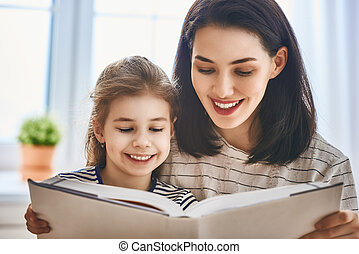 mother and daughter reading a book - Pretty young mother and...