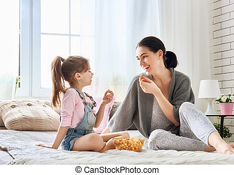 Mother and daughter eating popcorn - Happy loving family....