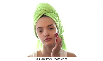 a young girl with a towel on his head causing facial cream...