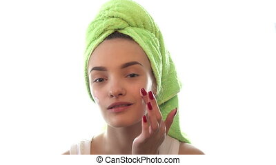 girl with towel on the hair with both hands causes the cream...