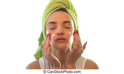 young girl with closed eyes causing face cream - young...
