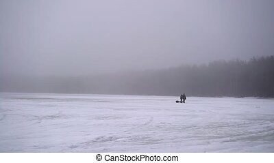 Unrecognizable people walking on frozen lake ar winter