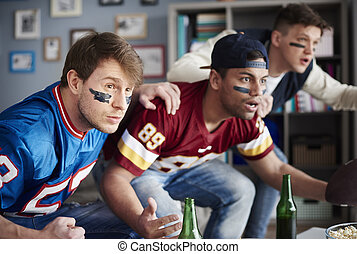Front view of excited men watching sports game