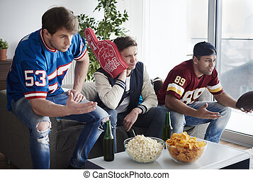 Group of friends together supporting football team