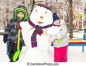 Two little fiends, kids making a snowman, playing and having...