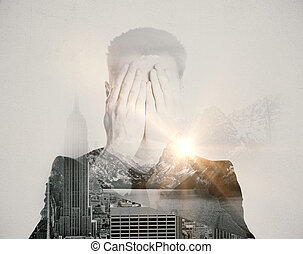 Fear concept - Man covering face with hands on abstract city...
