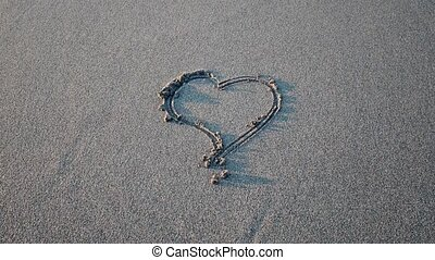 Heart drawn on the sand erasing wave