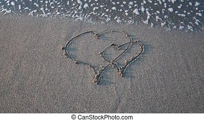 Two hearts drawn on the sand erasing wave