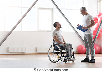 Smiling young disabled patient having conversation with his physical therapist