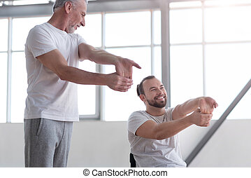 Professional physical therapist exercising with disabled man
