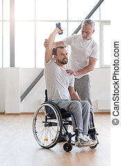 Powerful disabled man exercising with his coach in the gym