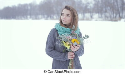Love with a girl in a gray sweater with a bouquet of flowers on a frozen lake