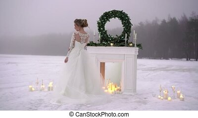 Young woman in white dress near fireplace decoration on...