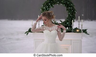 Young woman in white dress near fireplace decoration on frozen lake
