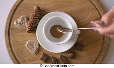 Wooden background of pouring hot coffee, candies and biscuit