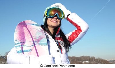 Snowboarder girl in glasses standing on a slope