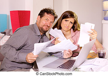Sad couple showing taxes looking camera