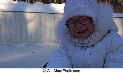 Little girl child riding a toboggan. Girl really like to ride on the toboggan. Girl laughs and emotes from the fast toboggan rides. Winter children's entertainment. Winter frosty sunny day in the park