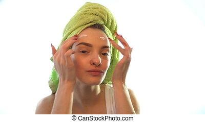 cute girl with a towel on her head smears face cream - cute...