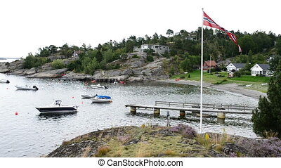 Small harbor with private speed boats and flag of Norway...
