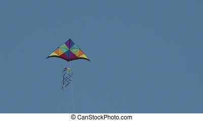 Colorful kite flying in blue sky during a sunny day
