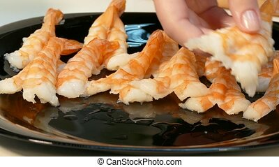 Large cooked shrimp spread on a black plate - Fresh shrimp...
