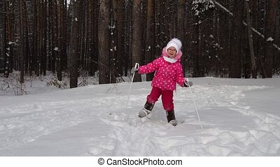 Girl child is learning to ski. But she do not always get and she falls on the snow. Beautiful day in the winter forest