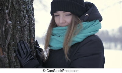 Happy girl in warm clothes standing near tree. Full hd video
