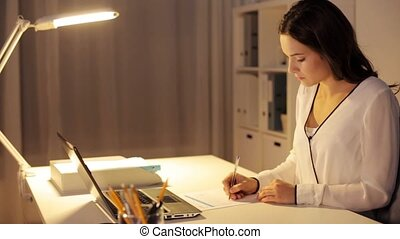 woman with calculator and papers at night office - business,...