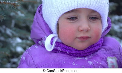 the little child is standing on the street in the winter and...